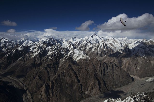 Argentinian Red Bull pilot Hernan Pitocco performs a wingover high above the Karakoram Range in North Pakistan. (Photo by Krystle Wright/Caters News)