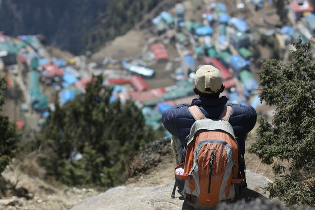 In this Monday, April 6, 2015 photo, a local Nepalese man sits above Namche, a village inhabited by mainly Sherpas, in the Everest region in Nepal. Climbers are returning to Mount Everest as the climbing industry recovers from last year's deadly disaster on the world's highest peak, a Nepalese mountaineering official said on April 1. The popular spring climbing season began last month and runs until the end of May. (Photo by Tashi Sherpa/AP Photo)