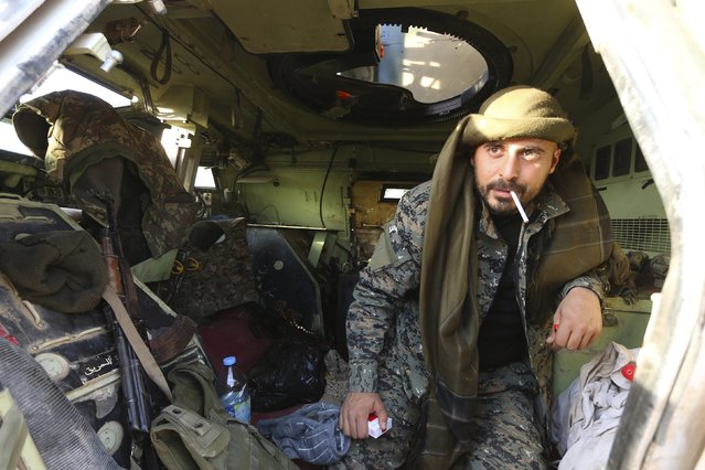 A Belgian fighter from the Democratic Forces of Syria holds a cigarette in his mouth inside a military vehicle in Ghazila village after taking control of the town from Islamic State forces in the southern countryside of Hasaka, Syria February 17, 2016. (Photo by Rodi Said/Reuters)