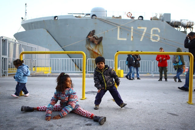 Refugee children play next to a Greek naval ship used as a shelter for refugees and migrants from bad weather conditions, at the port of the Greek island of Lesbos, January 13, 2017. (Photo by Elias Marcou/Reuters)