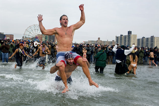 Swimmers jump into frigid waters at Coney Island beach in New York, Wednesday, January 1 2014, as they take part in the 111th Annual New Year's Day Polar Bear Plunge. (Photo by Craig Ruttle/AP Photo)
