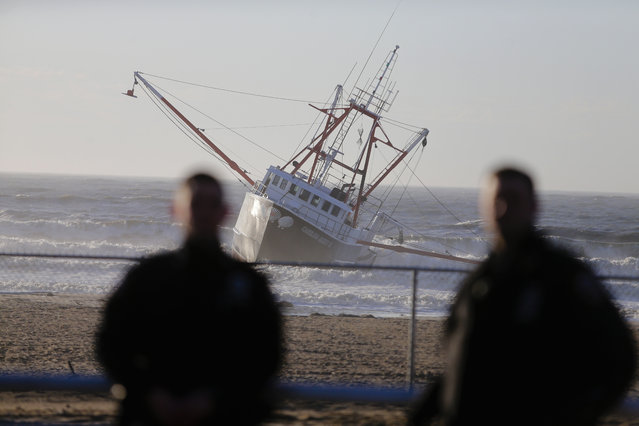 Police officers stand near a fishing boat, the Carolina Queen III, as it rests in shallow water just off Rockaway Beach, Thursday, February 25, 2016, in the Queens borough of New York. Authorities say a Coast Guard vessel overturned while assisting the fishing boat that ran aground in an inlet off New York City. (Photo by Frank Franklin II/AP Photo)