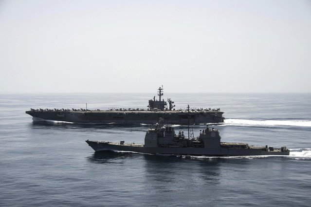 The aircraft carrier USS Theodore Roosevelt (CVN 71) and the guided-missile cruiser USS Normandy (CG 60) operate in the Arabian Sea conducting maritime security operations in this U.S. Navy photo taken April 21, 2015. (Photo by Mass Communication Specialist 3rd Class Anthony N. Hilkowski/Reuters/U.S. Navy)