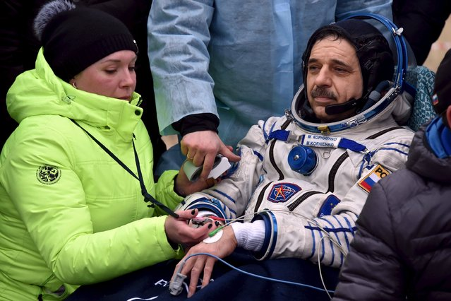 Medics check Russian cosmonaut Mikhail Korniyenko shortly after landing near the town of Dzhezkazgan (Zhezkazgan), Kazakhstan, March 2, 2016. (Photo by Kirill Kudryavtsev/Reuters)