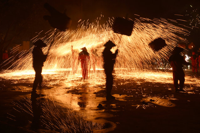 Folk artists holding lanterns perform under a shower of molten iron sparks during a local celebration ahead of the Chinese Lantern Festival, in Luzhou, Sichuan province, China on February 18, 2019. (Photo by Reuters/China Stringer Network)