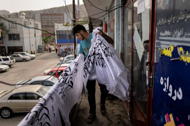 A worker collects newly hand printed Taliban flags in a workshop in Kabul's Jawid market, Afghanistan, Sunday, September 12, 2021. The small flag shop, tucked away in the courtyard of a Kabul market, has documented Afghanistan's turbulent history over the decades with its ever-changing merchandise. Now the shop is filled with white Taliban flags, emblazoned with the Quran's Muslim statement of faith, in black Arabic lettering. (Photo by Bernat Armangue/AP Photo)