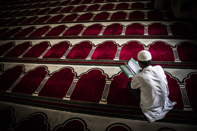 """""""Read between the lines"""". Manama, Bahrain. A man in a mosque reads the Koran during the holy month of Ramadan. (Photo by Mustafa Abdulhadi)"""