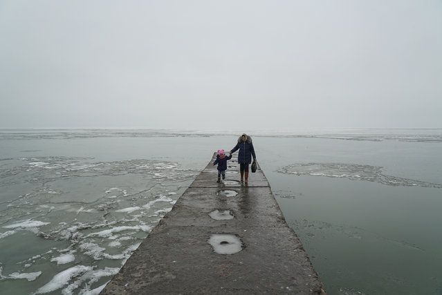 A woman with her child walks in the harbor of Mariupol, in the Sea of Azov, eastern Ukraine, Monday, Dece,ber 3, 2018. The Ukrainian military has been on increased readiness as part of martial law introduced in the country in the wake of the Nov. 25, 2018 incident in the Sea of Azov, in which the Russian coast guard fired upon and seized three Ukrainian navy vessels along with their crews. (Photo by Evgeniy Maloletka/AP Photo)