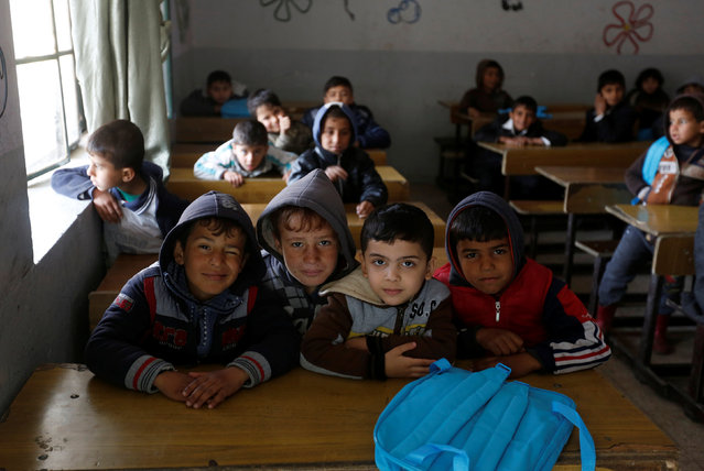 Schoolchildren react to a camera as they attend in a class after registering in school in Mosul, Iraq, January 23, 2017. (Photo by Muhammad Hamed/Reuters)