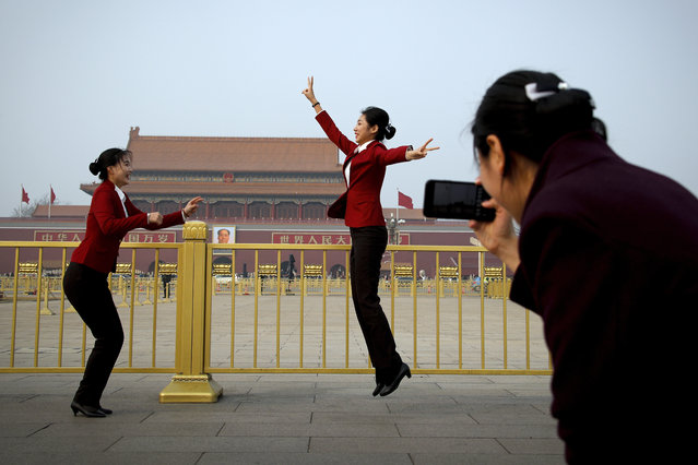 Hospitality staff jump as they pose for their colleague on Tiananmen Square during the opening session of the Chinese People's Political Consultative Conference (CPPCC) held at the Great Hall of the People in Beijing, Sunday, March 3, 2019. (Photo by Andy Wong/AP Photo)