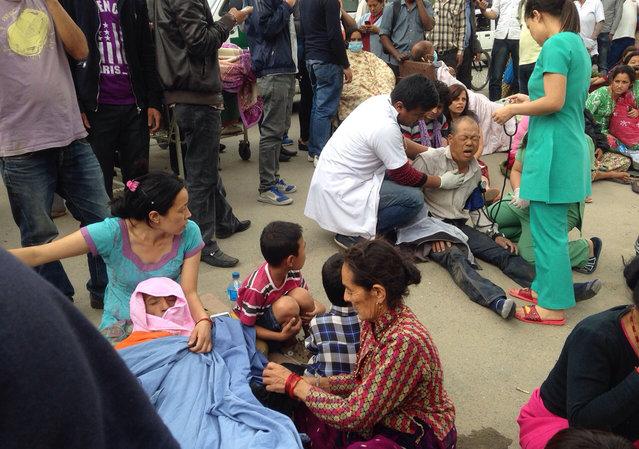 An injured man receives treatment outside the Medicare Hospital in Kathmandu, Nepal, Saturday, April 25, 2015. (Photo by Niranjan Shrestha/AP Photo)