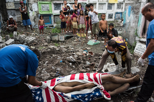 Shanty dwellers living inside the cemetery look at bodies being buried on January 24, 2017 in Manila, Philippines. Many bodies of victims of extrajudicial killings lay unclaimed in a morgue as funerals have had to deal with an upsurge in fatalities from the drug war. More than 6,000 Filipinos have been killed during the drug war in the Philippines as President Rodrigo Duterte recently threatened to impose martial law if necessary in his drive against drug users and dealers. Human rights activists have since placed the Philippines in the forefront of their concern as thousands of extrajudicial killings continue since the campaign against illegal drugs began in July last year. (Photo by Dondi Tawatao/Getty Images)