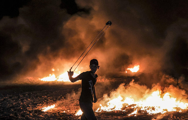 A Palestinian protester swings a slingshot near burning tyres following a demonstration along the border between the Gaza Strip and Israel east of Gaza City on August 28, 2021. (Photo by Mahmud Hams/AFP Photo)