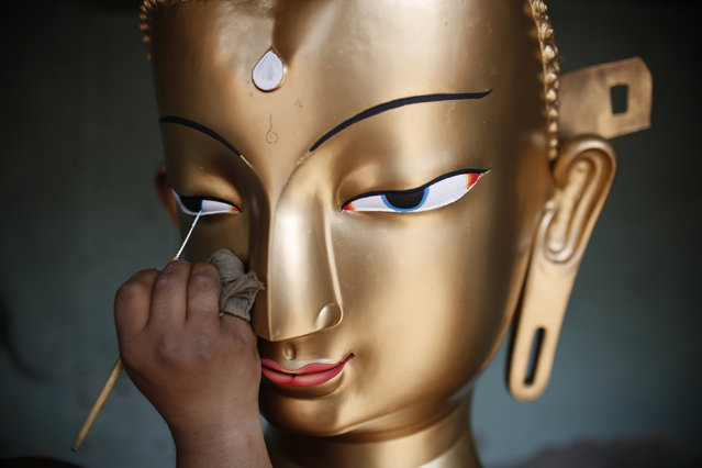 Saroj Shakya, 26, gives a finishing touch to the idol of Buddha ahead of the Samyak festival in Lalitpur, Nepal, March 11, 2016. (Photo by Navesh Chitrakar/Reuters)