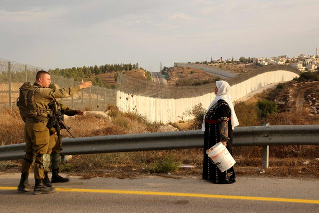 A Palestinian woman stands with others (not pictured) as they gather near an Israeli army checkpoint as they wait to reach their olives fields on the other side of Israel's separation barrier (background) after they received an special Israeli permission to harvest their olive trees, on October 13, 2021 near Bait A'wa village on the outskirts of the West Bank city of Hebron. (Photo by Hazem Bader/AFP Photo)