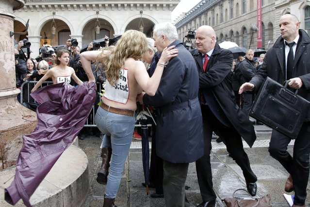 "FEMEN activists with Le Pen Top Fascist"" painted on their bodies appear as France's far-right National Front president Marine Le Pen places a wreath at Joan of Arc statue during its annual May Day march, in Paris, France, Friday, May 1, 2015. (Photo by Francois Mori/AP Photo)"