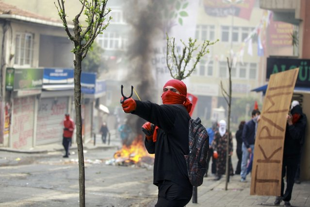 A protester uses a catapult during clashes with police in Okmeydani neighborhood in Istanbul, Turkey, May 1, 2015. (Photo by Huseyin Aldemir/Reuters)