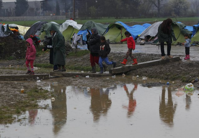 Migrants waiting to cross the Greek-Macedonian border, walk over muddy puddles in a makeshift camp, near the village of Idomeni, Greece March 15, 2016. (Photo by Ognen Teofilovski/Reuters)