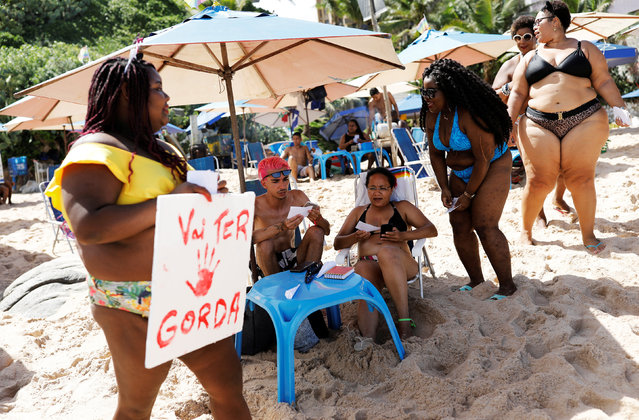 "A woman, member of ""Will be Fat"" movement, gives pamphlets to tourists as her mates take part in a protest against fatphobia on a beach in Salvador in Bahia state, Brazil, April 7, 2019. The movement aims to fight the prejudice suffered by people who are overweight and restore the self-esteem of women. (Photo by Nacho Doce/Reuters)"