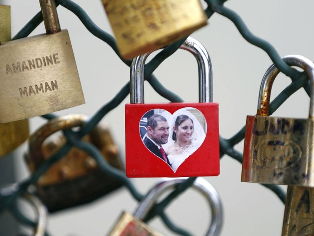 Padlocks have all different shapes and sizes, some couples customised them with their own wedding photos. (Photo by Charles Platiau/Reuters)