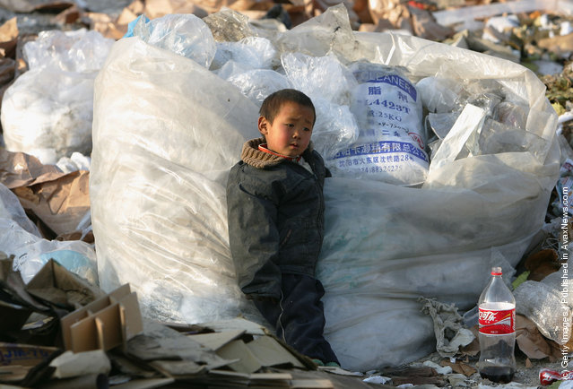 A Chinese kid of migrant workers plays at a refuse dump