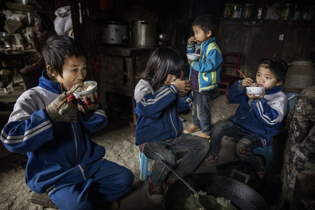 """""""Left behind"""" children from left to right, Luo Gan, 10, Luo Hongni, 11, Luo Lie, 5, and Luo Hongniu, 8, eat together at the family home on December 18, 2016 in Anshun, China. (Photo by Kevin Frayer/Getty Images)"""