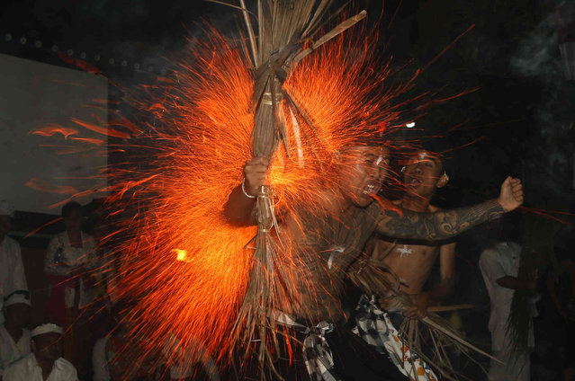 """A Balinese man reacts as he is hit with flaming coconut leaves during the fire fight ritual called """"Lukat Gni"""" before Nyepi in Klungkung, Bali, Indonesia, Wednesday, March 6, 2019. Bali's airport will close for 24 hours, the internet will be turned off and streets emptied as the predominantly Hindu island in Indonesia observes its New Year with an annual day of silence. (Photo by Firdia Lisnawati/AP Photo)"""