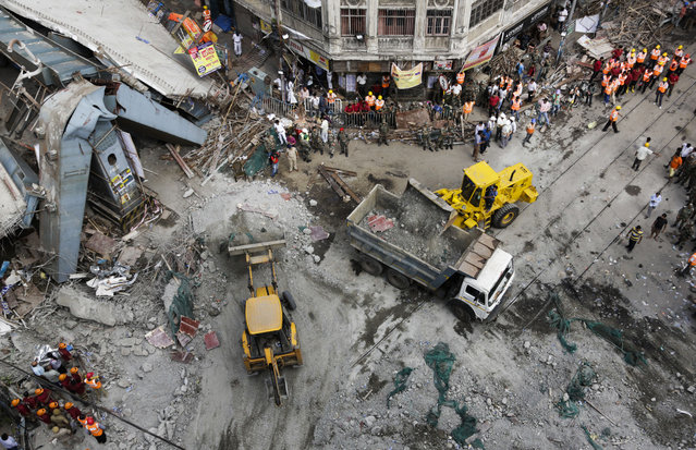 Excavator machines remove debris of a partially collapsed overpass in Kolkata, India, Friday, April 1, 2016. (Photo by Bikas Das/AP Photo)