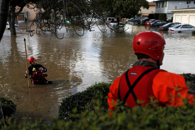 A firefighter with the San Jose Fire Department walks in a flooded neighborhood after heavy rains overflowed nearby Coyote Creek in San Jose, California, U.S., February 21, 2017. (Photo by Stephen Lam/Reuters)