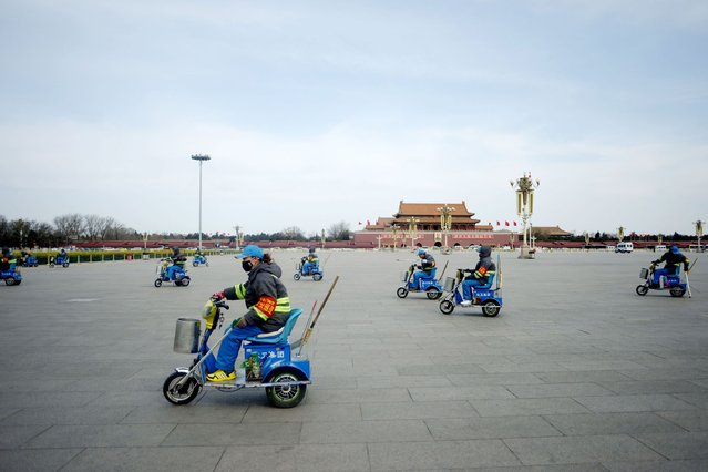 A group of cleaners clean the ground as they ride tricycles after the closing session of the Chinese People's Political Consultative Conference (CPPCC), in Tiananmen Square in Beijing on March 12, 2014. China has banned delegates to its annual rubber-stamp parliament from holding banquets, an official said as the government tries to improve its image following regular corruption scandals. (Photo by Wang Zhao/AFP Photo)