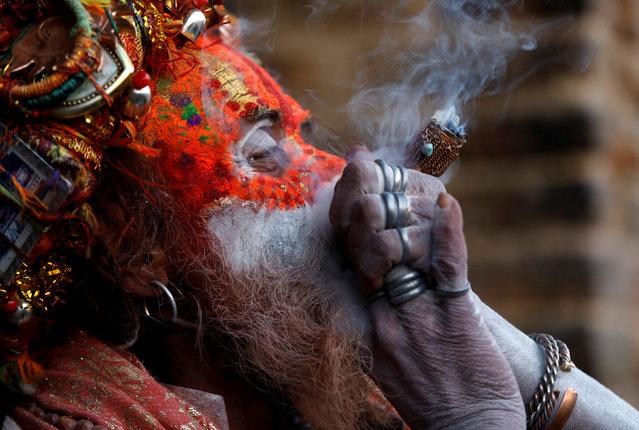 A Hindu holy man, or sadhu, smokes marijuana at the premises of Pashupatinath Temple during the Shivaratri festival in Kathmandu, Nepal March 4, 2019. (Photo by Navesh Chitrakar/Reuters)