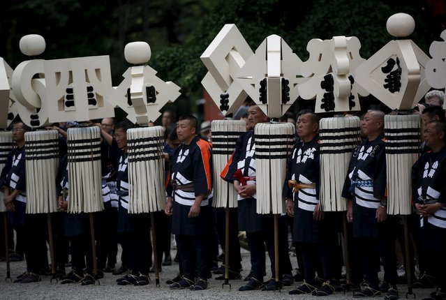 "Men wearing costume of traditional firefighters hold ""Matoi""company standards, as they attend a memorial service for firefighters at Sensoji temple in Tokyo's downtown of Asakusa May 25, 2015. (Photo by Issei Kato/Reuters)"