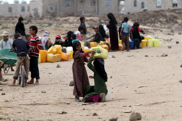 A girl helps her sister to carry a jerrycan filled with water from a public tap amidst an acute water shortage in Sanaa May 13, 2015. (Photo by Mohamed al-Sayaghi/Reuters)