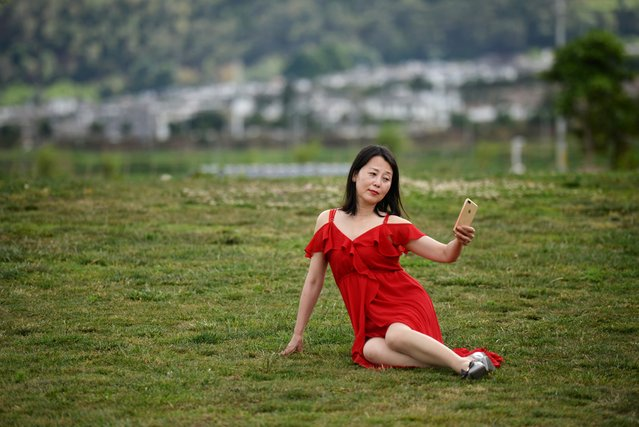 A woman takes selfies with a mobile phone near Erhai Lake in Dali Bai Autonomous Prefecture, Yunnan province, China on June 15, 2019. (Photo by Tingshu Wang/Reuters)