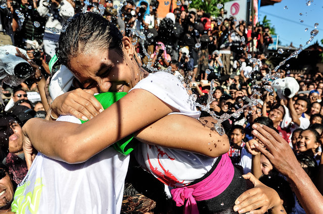 """A young Balinese couple embrace during the Kissing Festival known as """"Omed-Omedan"""" at Sesetan village on April 1, 2014 in Denpasar, Bali, Indonesia. (Photo by Agung Parameswara/Getty Images)"""
