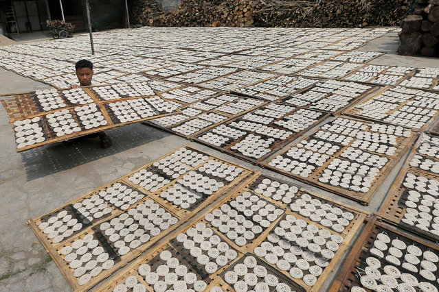 A worker dries crackers before frying at a home factory on the outskirts of Jakarta, Indonesia, Friday, June 21, 2019. (Photo by Tatan Syuflana/AP Photo)