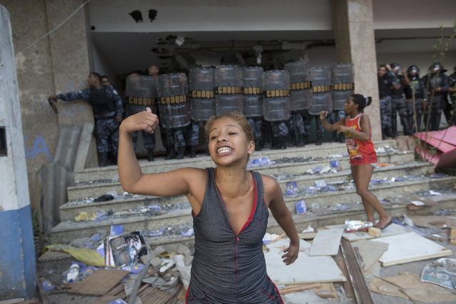 A woman shouts asking for help during an eviction in Rio de Janeiro, Brazil, Friday, April 11, 2014. Squatters in Rio de Janeiro are clashing with police after a Brazilian court ordered that 5,000 people be evicted from abandoned buildings of a telecommunications company. Officers have used tear gas and stun grenades to try to disperse the families. (Photo by Silvia Izquierdo/AP Photo)
