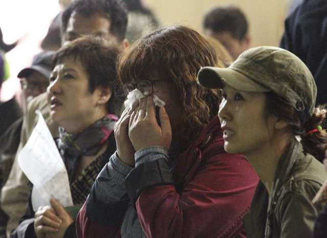 A mother weeps as she and others search for their children's names among a list of survivors rescued from a ferry that sank off the country's southern coast, at Danwon high school in Ansan, South Korea, Wednesday, April 16, 2014. (Photo by Ahn Young-joon/AP Photo)