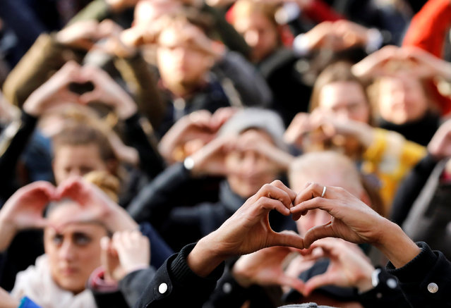 People make hearts with their fingers during a ceremony outside the Bourse, commemorating the first anniversary of the bomb attacks in Brussels metro and the Belgian international airport of Zaventem, in Brussels, Belgium, March 22, 2017. (Photo by Yves Herman/Reuters)