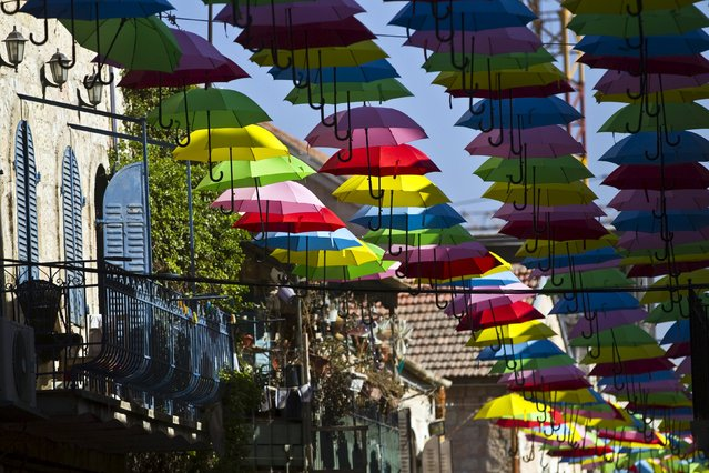 Colourful umbrellas decorate a pedestrian mall in downtown Jerusalem June 30, 2015. The installation, made of some 1,000 umbrellas, is part of a campaign to attract visitors to the city's center, a statement from the Jerusalem Municipality said on Tuesday. (Photo by Ronen Zvulun/Reuters)