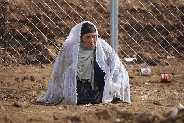 A displaced Iraqi woman from Mosul waits upon her arrival at the Hamam al-Alil camp on March 20, 2017, during the government forces ongoing offensive to retake the western parts of the city from Islamic State (IS) group fighters. The forces have recaptured several neighbourhoods from IS since starting the push for west Mosul last month, but the battle for the Old City, with its warrens of alleyways, was always expected to be tough. (Photo by Ahmad Al-Rubaye/AFP Photo)