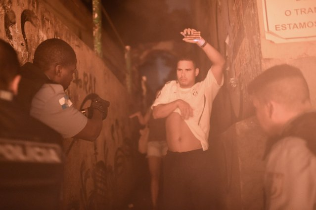 Brazilian Police Special Force members detain a man during a violent protest in a favela near Copacabana in Rio de Janeiro, Brazil on April 22, 2014. Violent protests broke out in Rio's landmark beachfront district, Copacabana, following the death of a resident last weekend during clashes with the Army in a nearby favela. (Photo by Christophe Simon/AFP Photo)