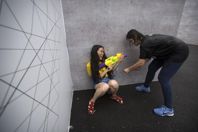 A player fires her water gun as she is cornered by another player pretending to be a zombie as they participate in a battle maze in Beijing, Saturday, July 4, 2015. Participants in the game are divided into teams of aliens, humans, and zombies. Each player aims to soak each other with water guns in the large outdoor maze, which organizers said was inspired by the online and mobile video games that are increasingly popular with China's youth. (Photo by Mark Schiefelbein/AP Photo)