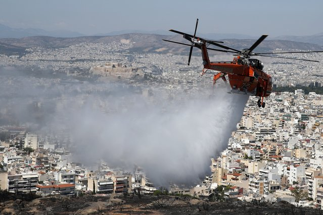 An helicopter drops water over a hill after a wildfire in the eastern Athens suburb of Vironas as the ancient Acropolis hill is seen in the background on Wednesday, August 28, 2019. The weather has helped fuel dozens of wildfires across the country as forest fires are common in Greece during the hot, dry and windy summer months. (Photo by Thanassis Stavrakis/AP Photo)