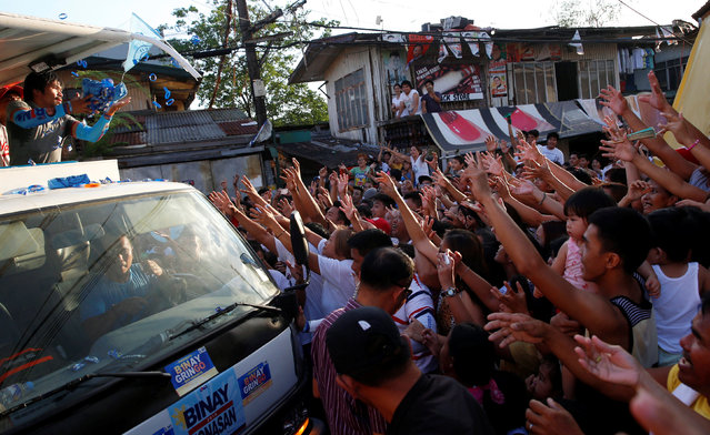 Filipino boxer and Senatorial candidate Manny Pacquiao throws election souvenir wrist bands and shirts to supporters during election campaigning in Malabon Metro Manila in the Philippines May 6, 2016. (Photo by Erik De Castro/Reuters)