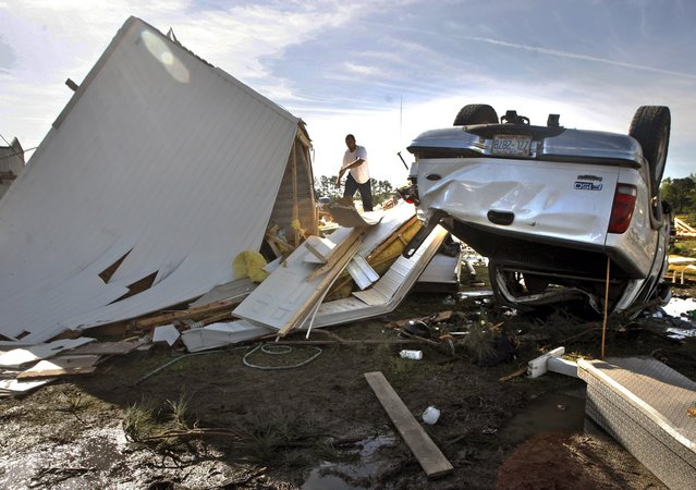 A man tries to salvage belongings from a overturned mobile home in Greenville, N.C. on Saturday, April 26, 2014 after a tornado touched down along Black Jack Simpson Road on Friday. Officials said multiple tornadoes damaged more than 200 homes the previous day and sent more than a dozen people to the emergency room. (Photo by Aileen Devlin/AP Photo/The Daily Reflector)