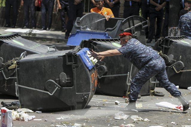 A policeman removes a barricade built with garbage bins by protesters against a hike in electricity prices in Yerevan, Armenia, July 6, 2015. Police forces pushed protesters from the main avenue after a standoff lasting two weeks, local media reported. (Photo by Hayk Baghdasaryan/Reuters/Photolure)
