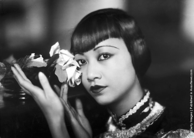 1935: American film star, Anna May Wong (1905 - 1961) poses with a cut rose