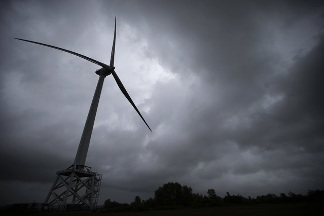 Rain clouds are seen in the sky where a Haliade 150 offshore wind turbine operates at Alstom's offshore wind site in Le Carnet, on the Loire Estuary, near Saint Nazaire, western France, April 27, 2014. (Photo by Stephane Mahe/Reuters)