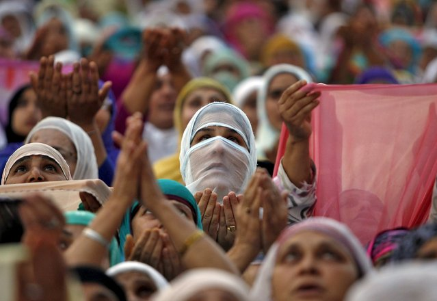 Kashmiri Muslim women pray upon seeing a relic, believed to be a hair from the beard of the Prophet Mohammad, displayed to devotees on the death anniversary of Hazrat Ali at Hazratbal shrine during the holy month of Ramadan in Srinagar July 9, 2015. Hundreds of Kashmiri Muslims on Thursday thronged to the Hazratbal shrine which houses what is believed to be a relic from the beard of Prophet Mohammed to offer prayers on the occasion of death anniversary of Hazrat Ali, son-in-law of Prophet Mohammad. (Photo by Danish Ismail/Reuters)